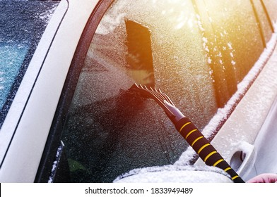 Cleaning an icy window on a car with ice scraper. Snow scraper. Cold snowy and frosty morning. Frozen car window.