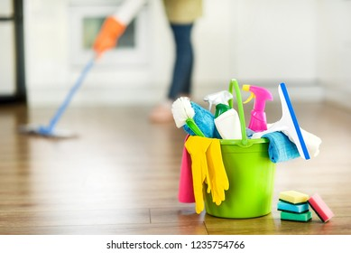 Cleaning items on floor in modern kitchen. Woman maid or charwoman blured in background. Bucket, brush, washcloth, spray.