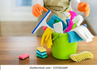 Cleaning items on wooden table in modern kitchen.  Woman house work or charwoman blured in background. Bucket, brush, washcloth, spray.