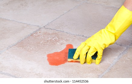 Cleaning up juice spill  on tile floor with sponge
