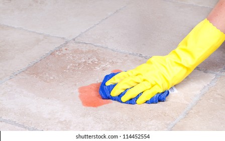 Cleaning up juice spill  on tile floor with cloth