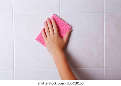 Cleaning kitchen tiles with sponge