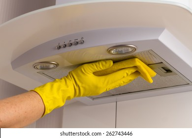 Cleaning kitchen. Washing kitchen hood in yellow gloves.