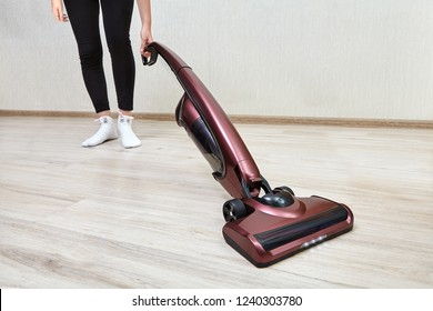 Cleaning lady in black leggings cleans dust in an empty room using a cordless handheld vacuum with led lights on.