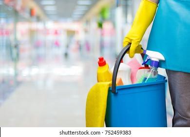 Schoonmaakster met een emmer en reinigingsproducten op wazige achtergrond.