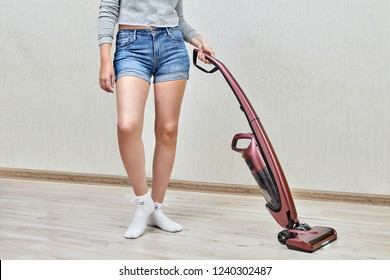 Cleaning lady in denim shorts is making household cleaning with help of modern handheld vacuum cleaner with led lights on.