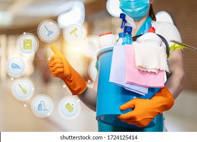 A cleaning lady in a mask shows the quality of work on a blurred background.