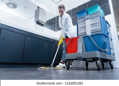Cleaning lady mopping the floor in restroom cleaning the toilet