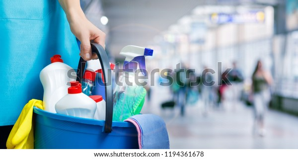 Reinigungskraft mit Reinigungsmitteln auf unscharfem Hintergrund.