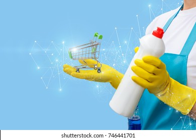 Cleaning lady shows the shopping cart and cleaning products on a blue background.