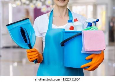 The cleaning lady standing with a bucket and with tool on blurred background.