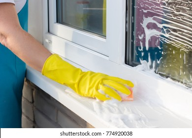 Cleaning lady from the street washes the window sill.