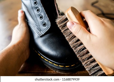 Cleaning leather boots with a shoe brush.