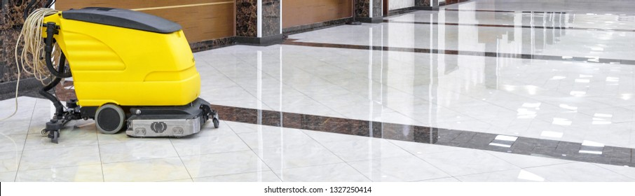 Cleaning machine in an office lobby. Cleaned floor in the interior of company or luxury hotel. Yellow vacuum equipment for cleaning on a shiny marble floor. Concept of professional cleaning service.
