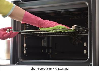 オーブンの掃除。家庭の掃除用手袋をはめた女性の手が炉の中を掃除する。台所でオーブンをきれいにしなさい。