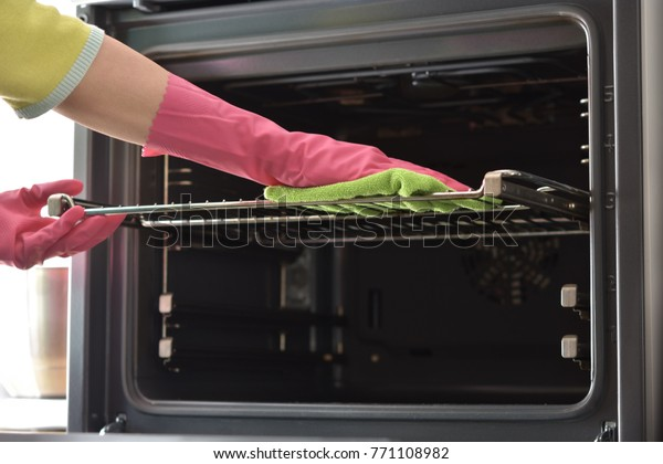 Cleaning the oven. Woman's hand in household cleaning gloves cleans oven inside. Clean oven in kitchen.