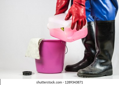 A cleaning person in a blue rubber protective suit, with  red rubber gloves and black rubber boots tilts a red, corrosive industrial cleaner in a plastic bucket.