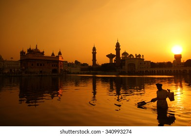 Cleaning the pool of the Golden Temple during sunset, Amritsar, India.