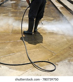 Cleaning with pressure water jet the pavement of the city streets. Municipal cleaning service