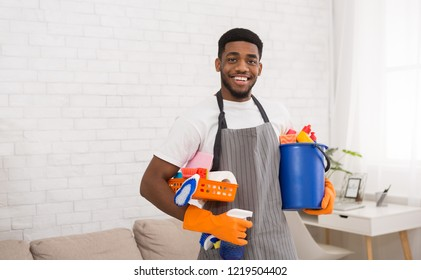 Cleaning products. Cheerful african-american guy cleaner holding lots of detergents, ready for housecleaning, copy space
