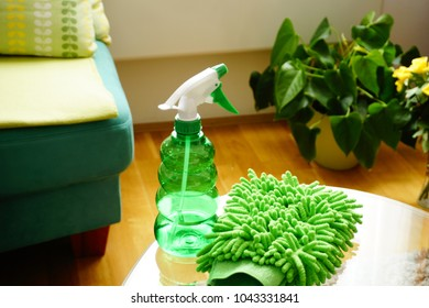 Cleaning products, green glove sponges for cleaning and a environmental skin friendly detergent in a green bottle on a glass table in the living room, prepared for cleaning home