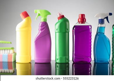 Cleaning products. Home cleaning concept. Wooden background. Gray tile floor. Place for typography and logo.