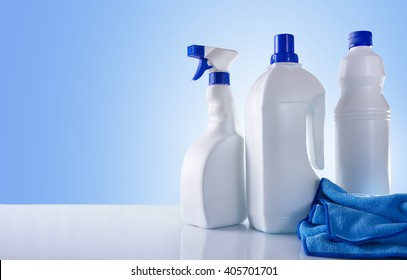 Cleaning products on white table and blue background overview. Front view. Horizontal composition.