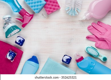 Cleaning products on wooden background with copyspace in the middle