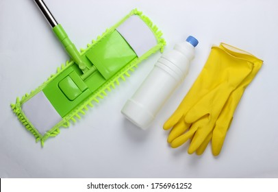 Cleaning products. Plastic green mop, gloves, bottle of detergent on white background. Disinfection and cleaning in the house. Top view