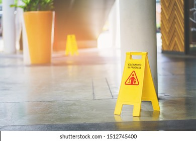cleaning in progress sign on yellow plastic board on floor
