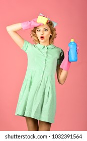Cleaning, retro style, purity. Cleanup, cleaning services, wife, gender. Pinup woman hold soup bottle, sponge. Retro woman cleaner on pink background. Housekeeper in uniform with clean spray, sponge.