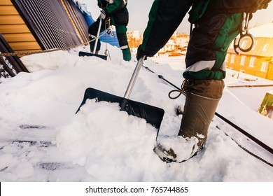 Cleaning roofs of buildings from snow, ice in the winter with a shovel.