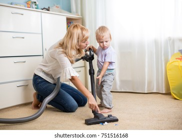 Cleaning up the room together - mother and her kid boy with vacuum cleaner