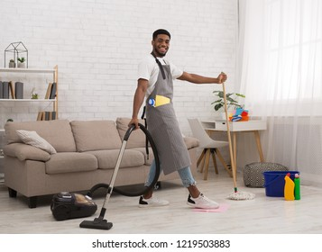 Cleaning service. Cheerful african-american man janitor cleaning house with vacuum cleaner and mop simultaneously