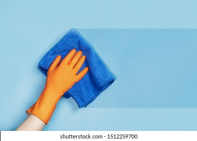 The cleaning service concept. Hand in rubber glove wipes the surface of the blue. - Shutterstock ID 1512259700