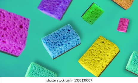 Cleaning service concept with cleaning sponges flying on blue green background