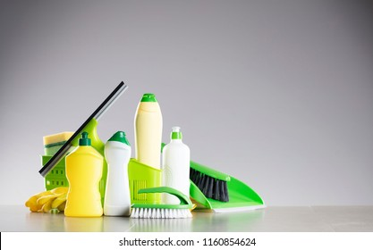 Cleaning service concept. Yellow, green and white cleaning products on gray background. Place for typography.