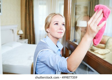 Cleaning service. hotel staff clean glass door from dust