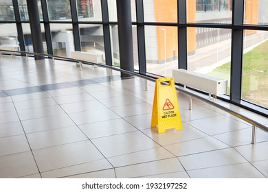 Cleaning service indoors. Yellow plastic caution sign - beware slippery on the floor at airport or shopping mall hall. Nobody