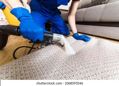 Cleaning service. Man janitor in gloves and uniform vacuum clean white carpet with professional equipment