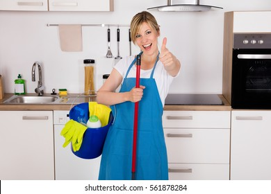 Cleaning Service Professional Housemaid Holding Gloves And Equipment In Kitchen At Home Showing Thumbs Up
