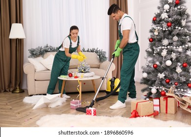 Cleaning service team working in messy room after New Year party