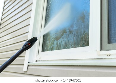 Cleaning service washing building facade and window with pressure water. Cleaning dirty wall with high pressure water jet. Power washing the wall. Cleaning the facade of the house. Before and after