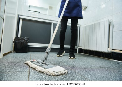 cleaning service. wiping toilet floor with mop