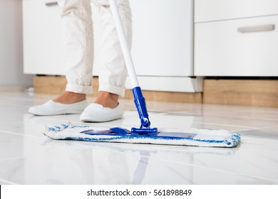 Cleaning Service Woman Mopping The Floor In Kitchen At Home