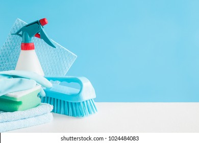 Cleaning set for different surfaces in kitchen, bathroom and other rooms. Empty place for text or logo on blue background. Cleaning service concept. Early spring regular clean up. Front view.