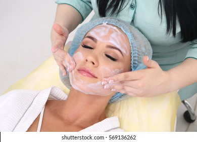 Cleaning the skin with foam, a beautiful woman in the beauty salon beauty. Cosmetologist job.
