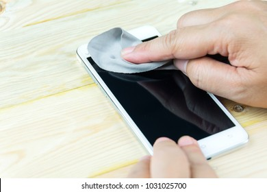 cleaning smart phone screen with microfiber cloth
