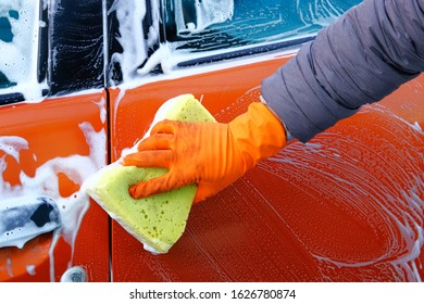 Cleaning with soap suds at self-service car wash. Man in rubber gloves washes his orange auto with yellow sponge. Soapy water runs down.