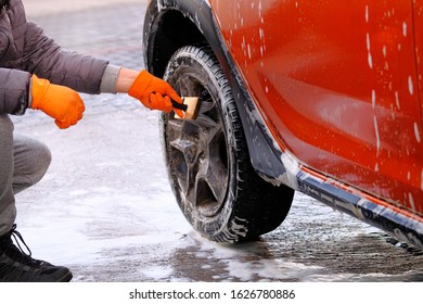 Cleaning with soap suds at self-service car wash. Man in rubber gloves washes black wheel of his orange car with brush. Soapy water runs down.